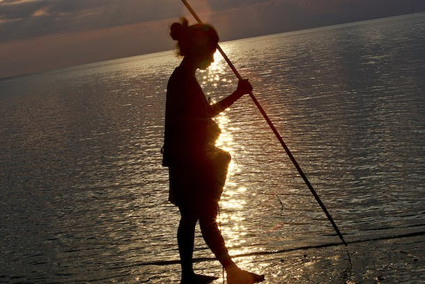 Woman Collecting Fish at Sunset