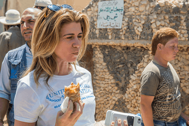 Georgie Benardete eating khubz in Za'atari Camp. Photo: Anton Demerjian for UN Foundation