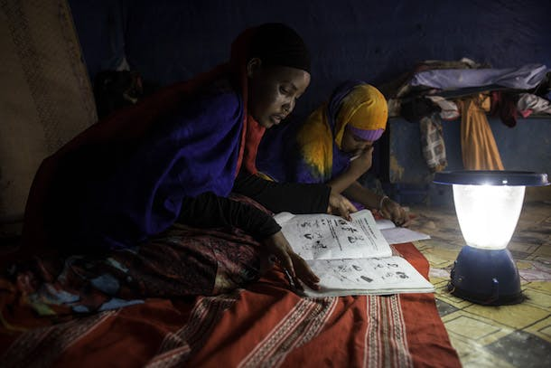 Students work on their homework with the help of a solar lantern at Awbare Refugee Camp in Somali region of Ethiopia 13 March 2014. Photo by Jiro Ose
