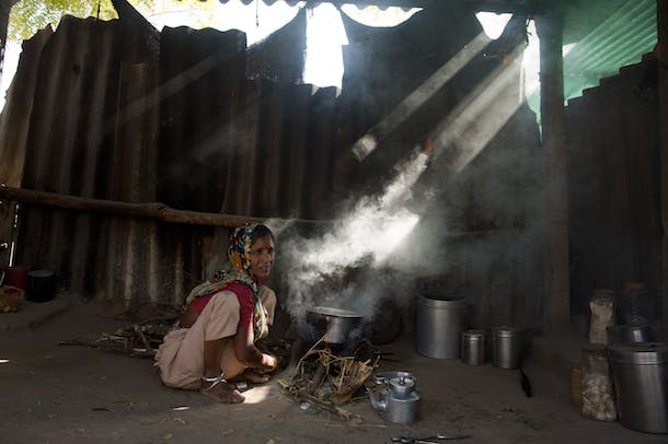 Dadam Ben tries to light the fire in the conventional cookstove in Ganeshpura village in District Mehsana in Indian State of Gujarat.