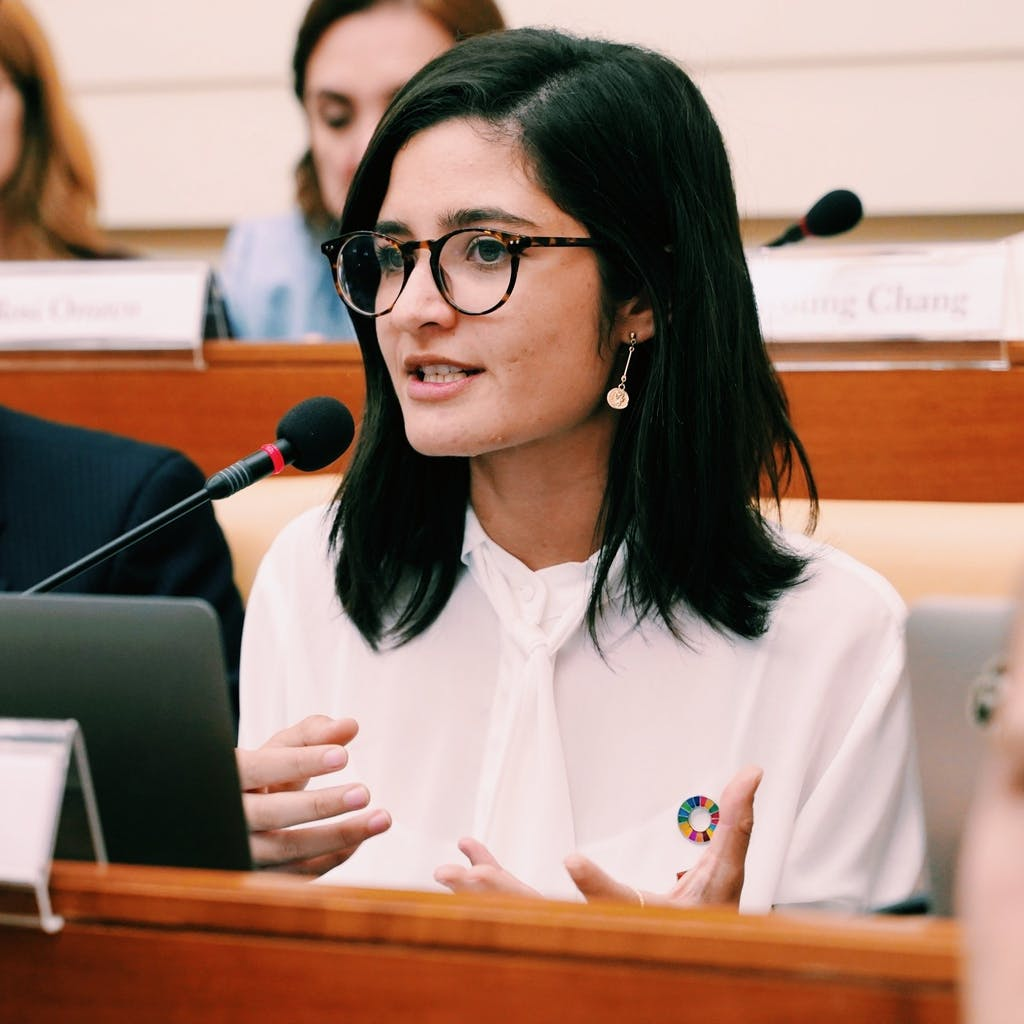 Young Spanish activist speaking against human trafficking while wearing a pin for the Sustainable Development Goals.
