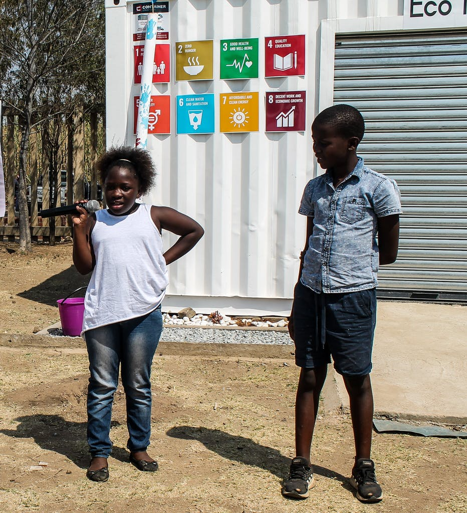 Two South African children speak at an event in front of the Sustainable Development Goals.