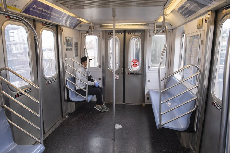 A man wearing a mask and gloves rides an empty subway train car