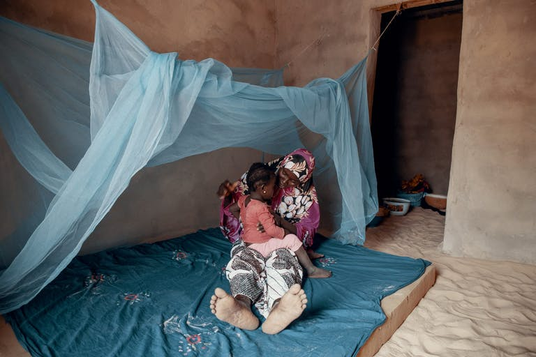 Woman with child under a bed net
