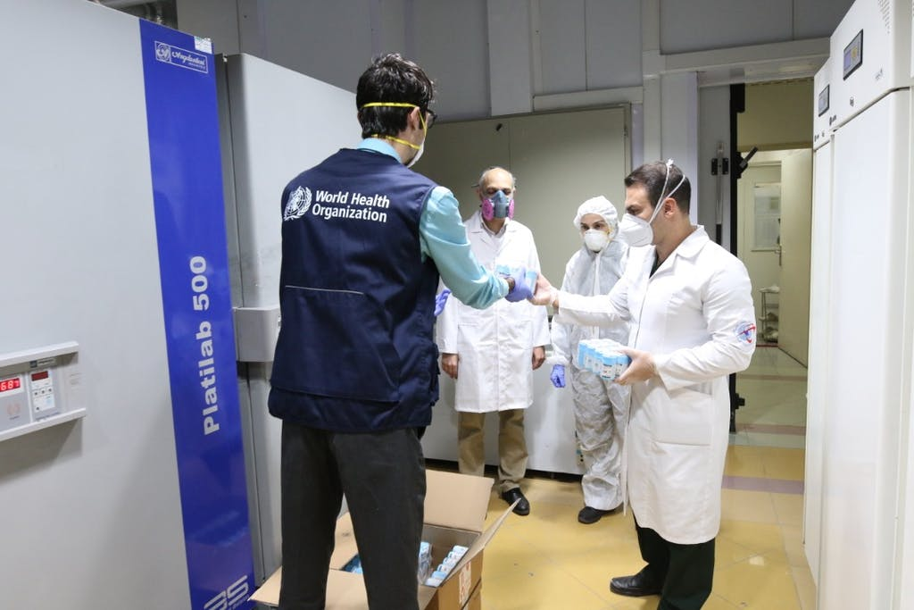WHO staffer gives iranian medical personell covid-19 equipment