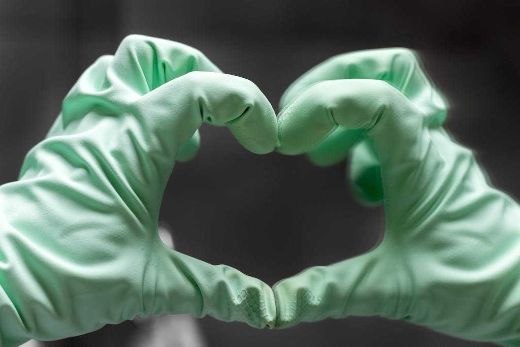 A hand in a mint green rubber glove shows a heart sign.