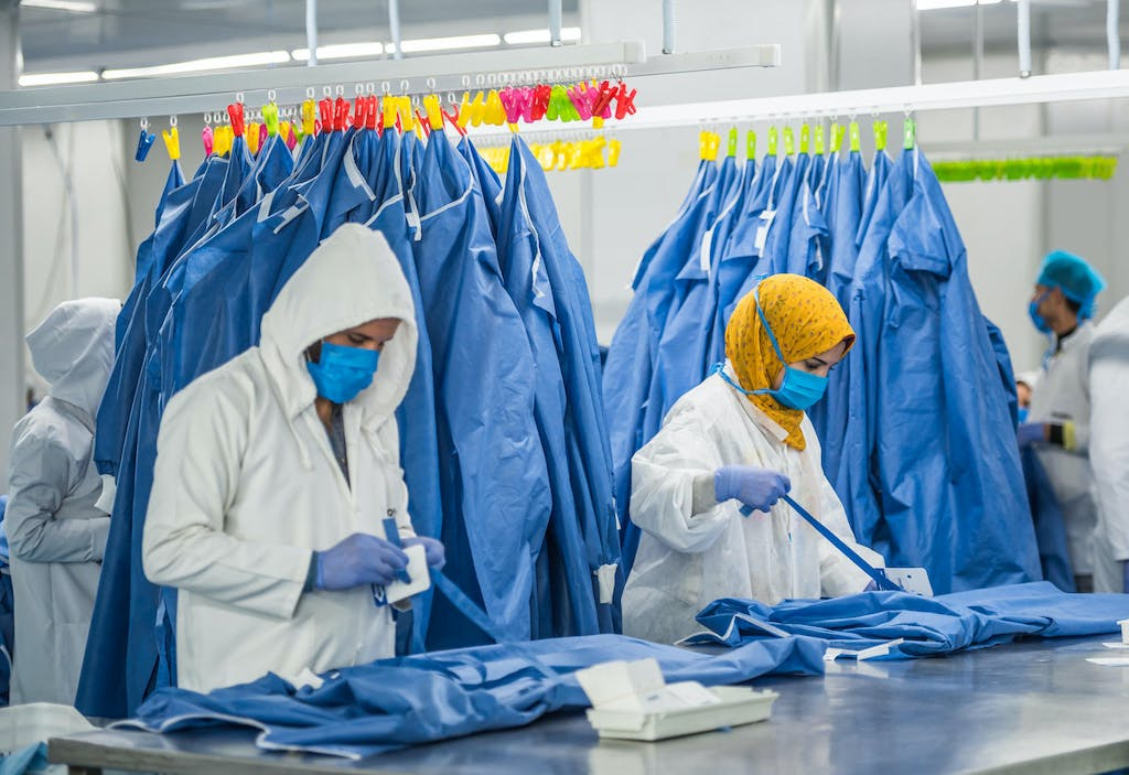 Health workers wearing masks and gloves prepare personal protective equipment