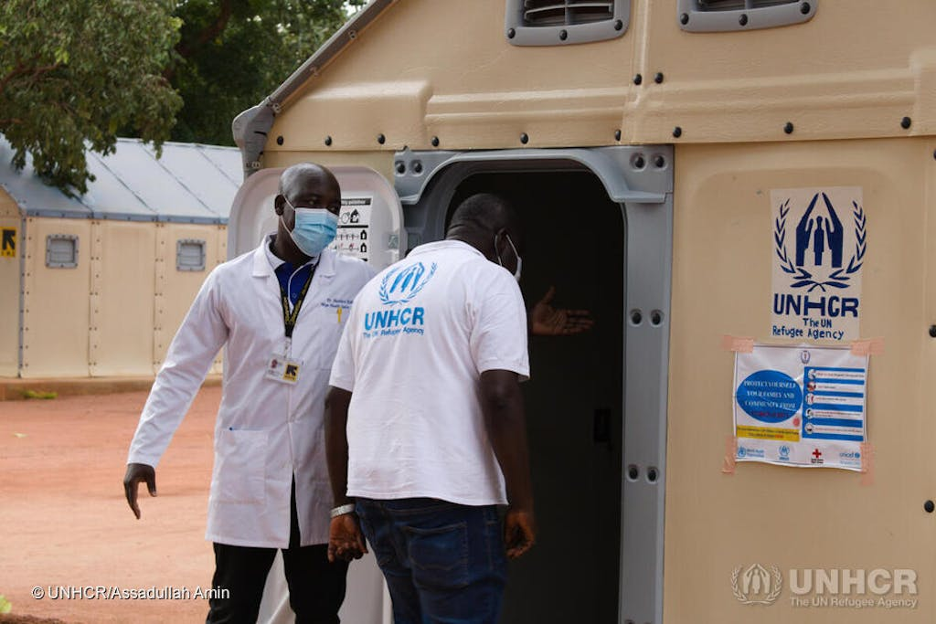 Two men wearing masks outside a UNHCR facility in South Sudan.